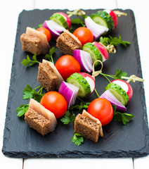 Appetizer with herring, rye bread and vegetables on skewers