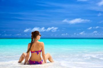 Beautiful young woman in bikini sitting on tropical beach