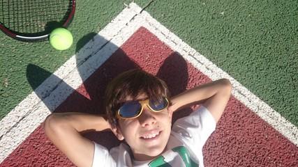 Niño con gafas de sol tumbado en pista de tenis
