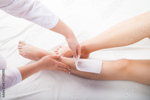 Beautician waxing  woman legs in spa salon - 72160113