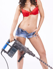 Young sexy female holding a drill