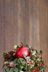 weihnachtliches gesteck vor holzhintergrund