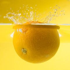 Nice orange falling into water. Yellow background.