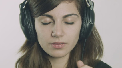 Attractive young sad woman listening to music on headphones