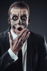 Surprised businessman with a makeup  skeleton