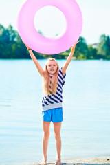 happy girl play swim ring at the beach