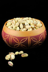 old ceramic bowl full of pistachios, on a black background