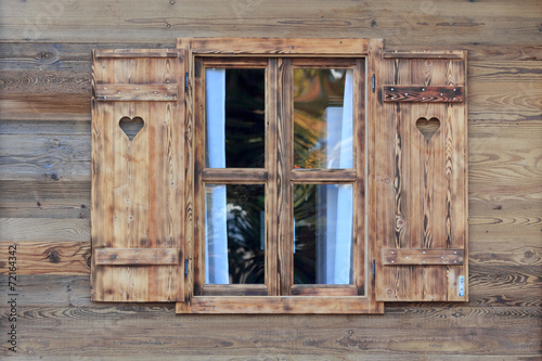 Foto op Aluminium Oude gebouw Window of a wooden hut with hearts in the blinds