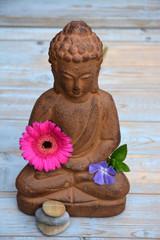 Boeddha standbeeld op oud houten achtergrond met Zen stenen