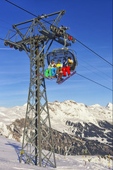 People on ski  and snowboards at cable car cabin on winter sport