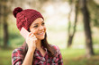 Young woman with beanie hat talking on the phone. No retouch.