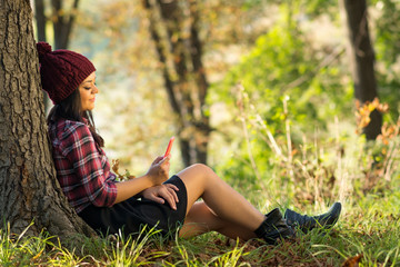 Young woman with smart phone relaxing in park in autumn