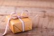 Leinwandbild Motiv Geschenk mit Schleife auf Holz - Copyspace