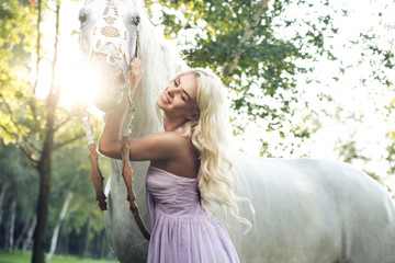 Satisfied woman hugging white horse
