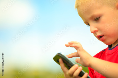 Little boy with mobile phone outdoor. Technology generation.