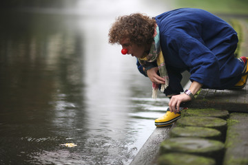 Upset clown on the river bank; street theater concept