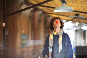 Young curly clown looking at the lamp