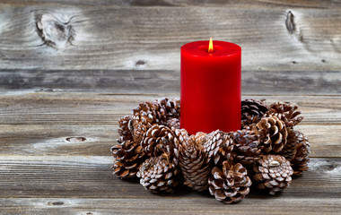 Burning Red Candle and Pine Cone Wreath for Christmas Season