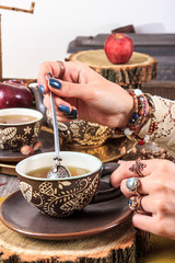 female hand stirred and squeezed into a cup of tea herbal ingre