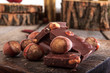 Pile of chocolate pieces with hazelnuts on wooden background