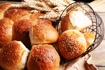 Tasty buns with sesame on rustic wooden background