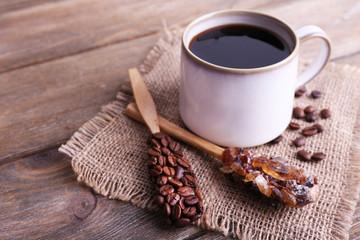 Mug of coffee on sackcloth on wooden background