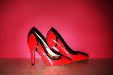 Pair of woman's red shoes on floor on red wall background