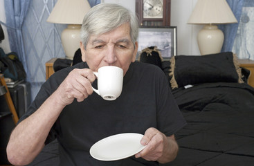 Senior man drinking from cup