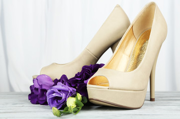 Beautiful woman shoes with flowers on light background