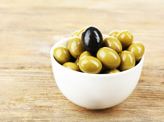 Individuality concept. Olive in bowl on wooden table