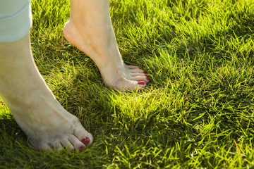 Woman standing barefoot in the grass