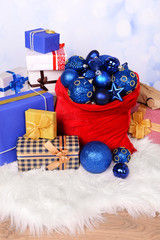 Red bag with Christmas toys and gifts on bright background