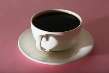 Cup of coffee on pink background