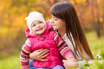 toddler girl and young mother play in the autumn park
