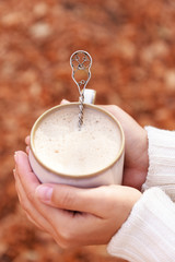 Woman holding cup of tasty hot drink, close-up,