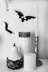 Candles and paper bats on table on white wall background