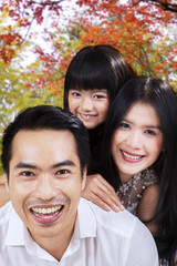 Attractive family smiling under autumn tree