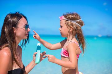 Little girl applying sunblock cream on her mom nose