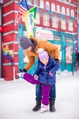Young dad and adorable little girl have fun on skating rink