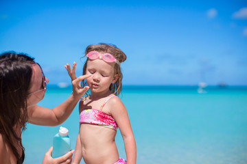 Young mother applying sunblock cream on her daughter's nose