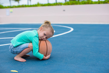 Little girl with basketball on court at tropical resort