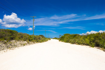 Deserted tropical road with white sand on Caribbean island