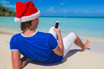 Back view of young man in santa hat with phone on tropical