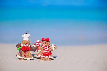 Christmas gingerbread man cookies on a white sandy beach