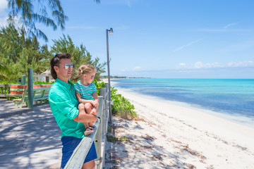 Young dad and his daughter walking on tropical island