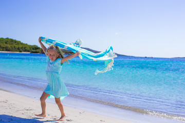 Adorable girl have fun with beach towel during vacation