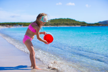 Adorable little girl at white beach during tropical vacation