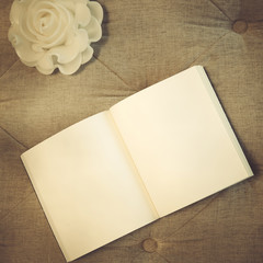 Blank book with rose candle on sofa