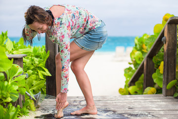 Young woman washes the sand from her feet on white beach