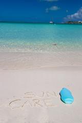 Suncare written on tropical white sand and suncream